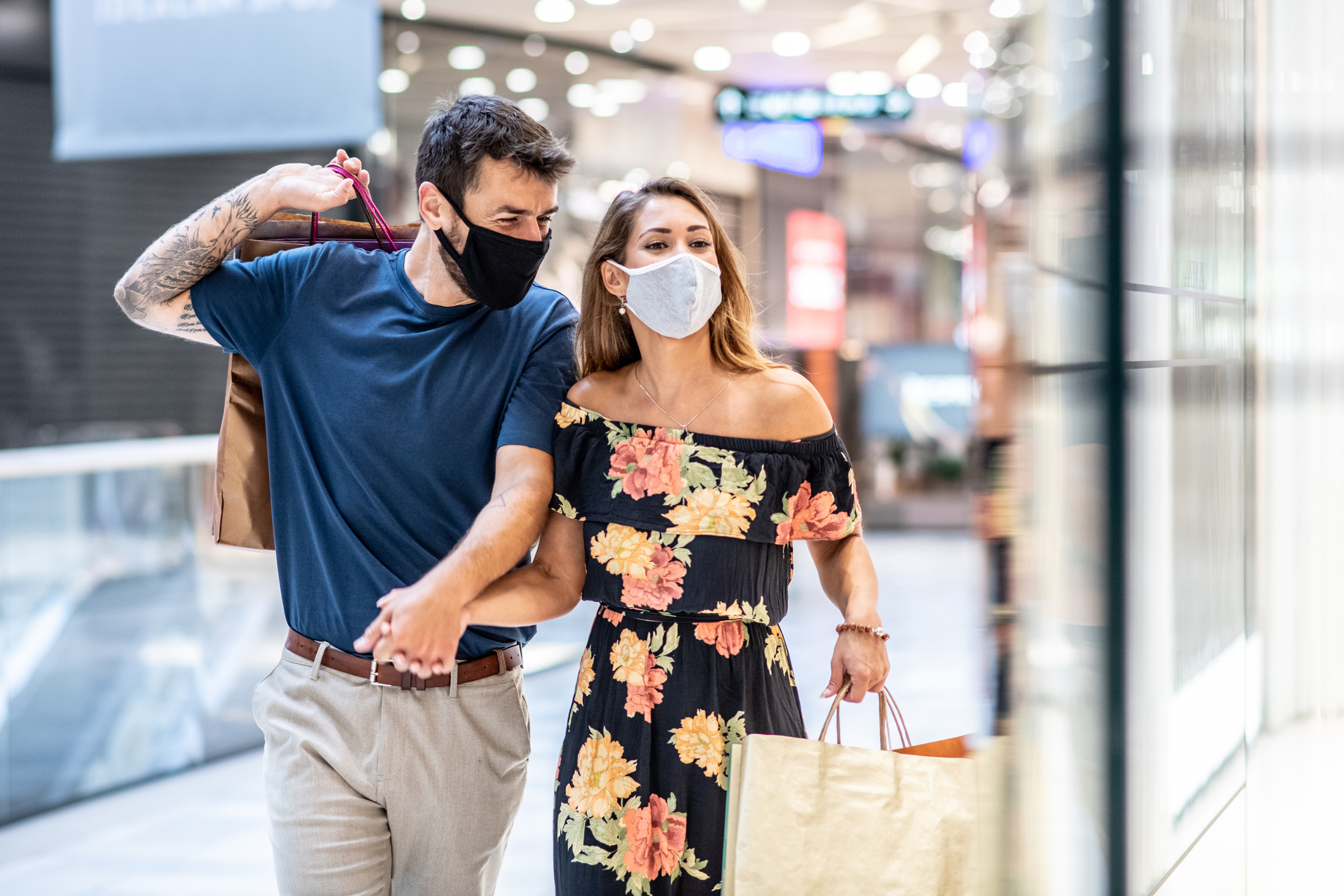 A Young Couple Is Carrying Shopping Bags With Masks On Their Faces And Walks, Shopping During A Pandemic
