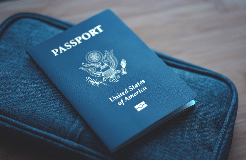Usa (united States Of America) Passport On Blue Travel Wallet, Wooden Background. Top View (above)