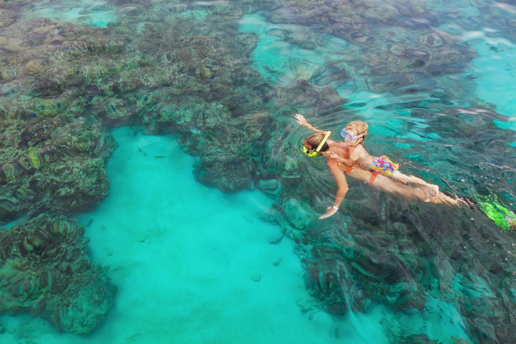 Mother, Kid In Snorkeling Mask Dive Underwater With Tropical Fishes